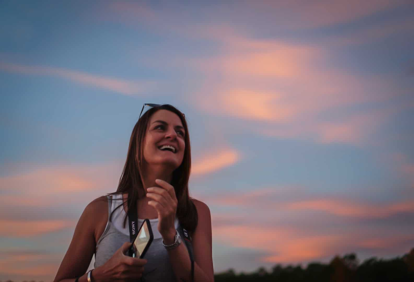 Portrait of Carole Dupre at sunset with blue sky and pink clouds, Clarks Hill Lake in South Carolina.